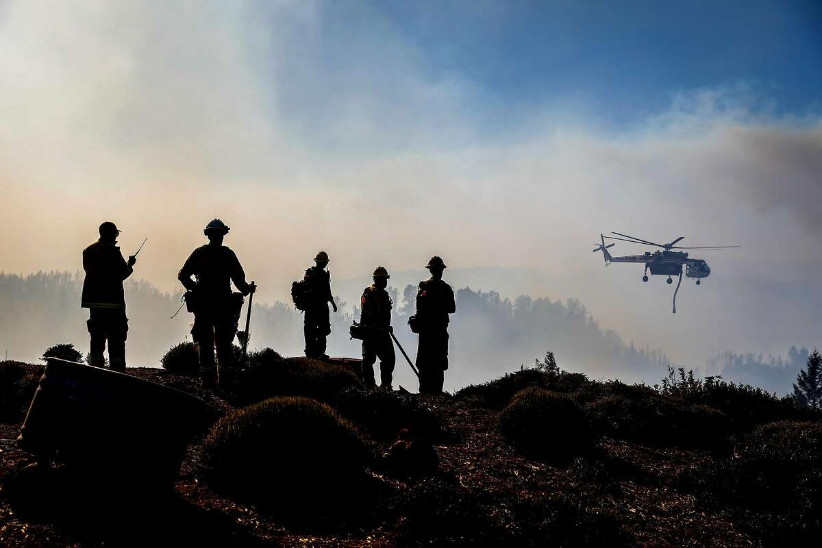 Firefighters watch as a helicopter drops water over the Kincade Fire near Ida Clayton Road in Calistoga (Napa County) in 2019.