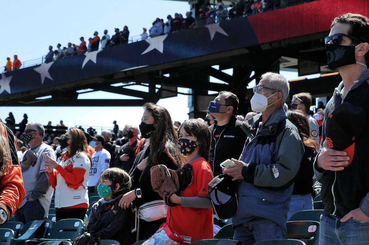 Fans stand for the national anthem Friday at Oracle Park in San Francisco. The city plans to expand capacity for outdoor events soon under the guidelines for the orange tier.