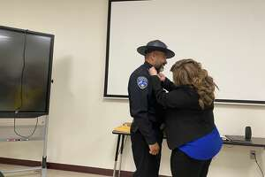 Sally Salinas places a pin on her husband, Jaime, in commemoration of his promotion to captain of patrol.