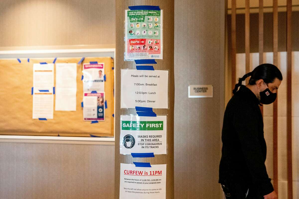 Signs remind visitors of meal times, curfew and mask requirements at an undisclosed hotel housing the homeless during the coronavirus pandemic in the Bay Area. The state's Homekey program has converted hotels and other building into housing for 8,000 homeless people.