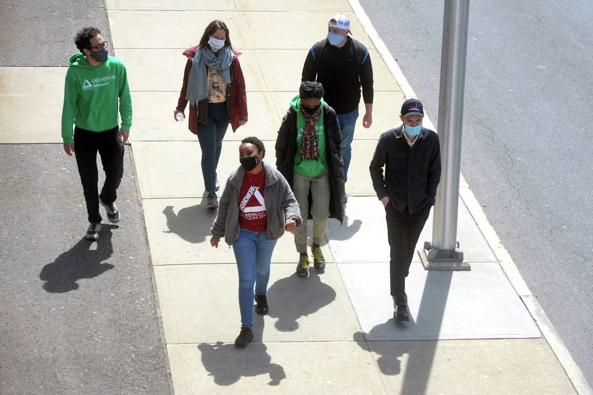 Six members of a new walking club walk along Water Street on their way from downtown to the end of Seaview Ave., and back, in Bridgeport, Conn. April 8, 2021. Organized by Groundwork Bridgeport, the club hopes enlist new participants as they plan similar outings around the city in the coming months.