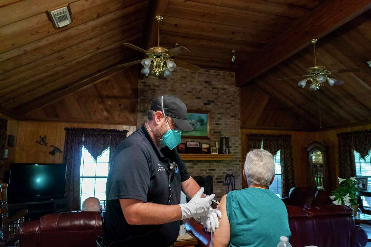 Chambers County paramedic Danny Burke administers a second dose of the Moderna COVID-19 vaccine to Leighanne Cobb, Tuesday, April 6, 2021, in Anahuac, TX. Cobb was receiving the vaccine at the same time as her 92-year-old father in her father's home as part of the county's mobile vaccination program. Cobb was initially reluctant to receive the vaccine, but her sister and niece convinced her that taking the vaccine was safe and important, she said. She's excited to go see a nephew that she has still not met.
