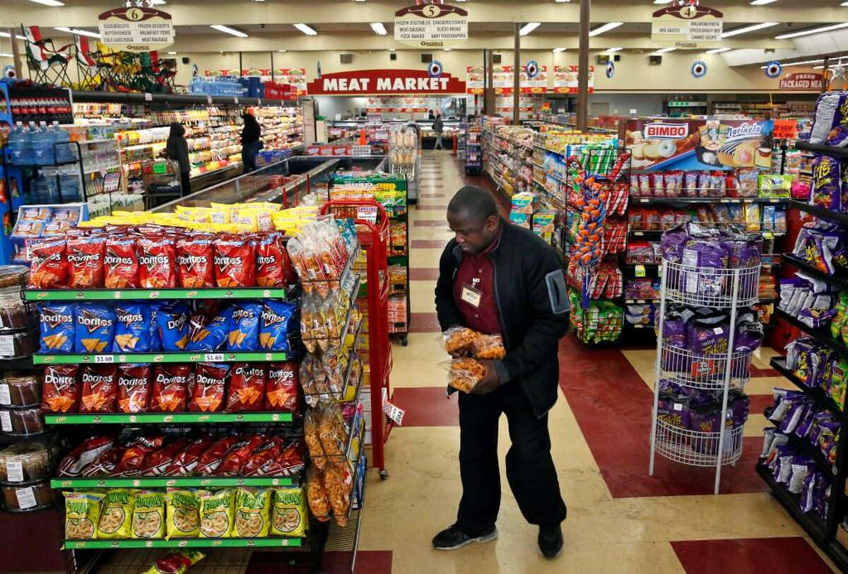 Store manager Wallace Miles stocks shelves at Gazzali's Supermarket June 28, 2017 in Oakland, Calif.