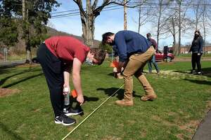 Quinnipiac University juniors Kyle Somogyi, left, and Mike Neumann of the student chapter of the American Society of Civil Engineers plant flags to mark a rough outline where society members are building a rain garden to protect runoff from the Albert Schweitzer Institute seeping into the Mill River, on April 9, 2021.