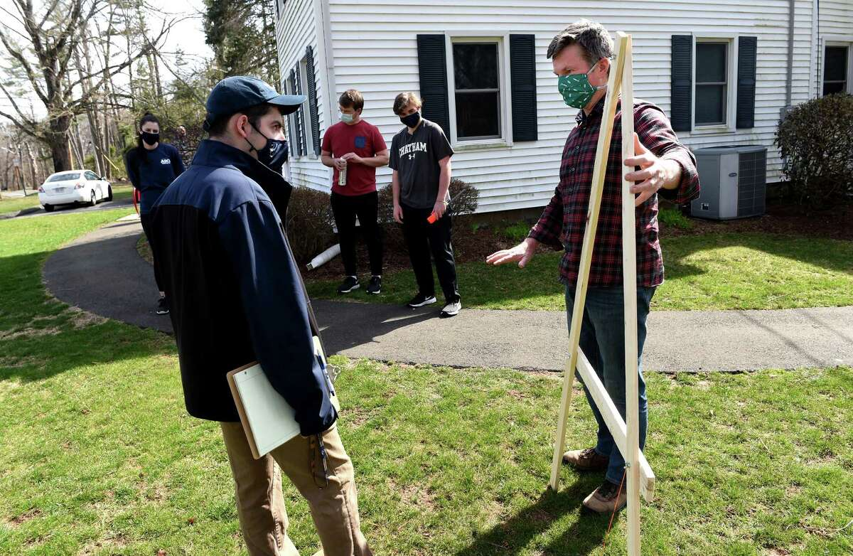 Sean Duffy, right, executive director of the Albert Schweitzer Institute, demonstrates a rudimentary level for mapping contours of the land to Michael Ciacciarella, president of the Quinnipiac University student chapter of the American Society of Civil Engineers, on April 9, 2021, where society members are building a rain garden to protect runoff from the Albert Schweitzer Institute seeping into the Mill River.