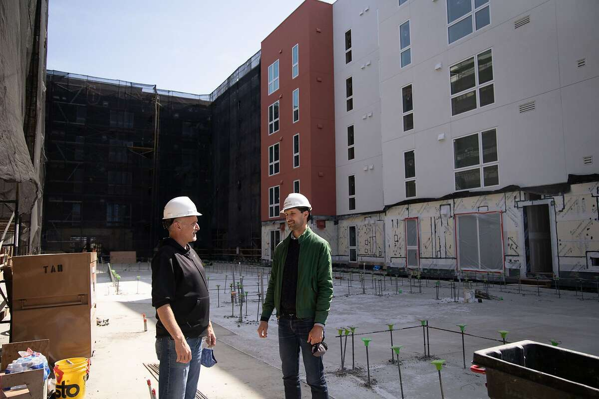 Andrew Meagher, vice president of design and engineering at Factory OS, talks with Jamie Hiteshew, director of development at Holliday, at a modular apartment building under construction near El Cerrito del Norte BART Station.