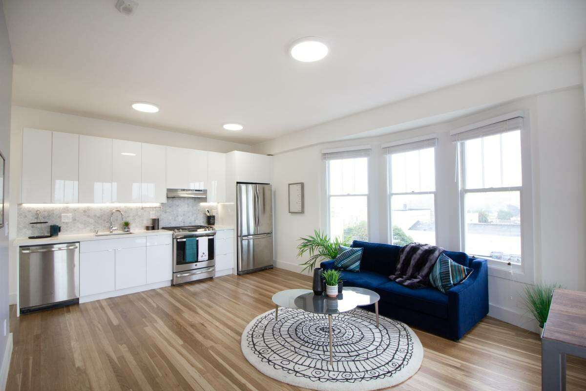 An open floor plan blends the kitchen/dining and living areas, which features lots of windows and natural light. The kitchen has new stainless steel appliances, including a dishwasher.