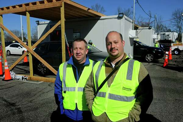 Jon Panzer and Mike Krebs work as volunteer EMTs with Stamford EMS Saturday, April 3, 2021, while helping vaccinate resident at the former Lord and Taylor in Stamford, Conn.