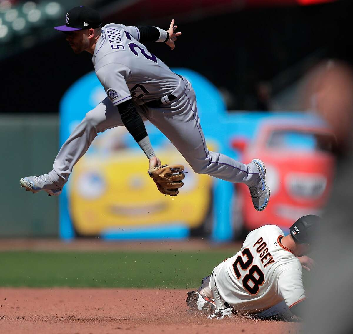 Trevor Story (27) goes airborne to avoid a sliding Buster Posey (28) at second base on a fielder's choice in the fifth inning as the San Francisco Giants played the Colorado Rockies at Oracle Park in San Francisco Calif., on Friday, April 9, 2021.