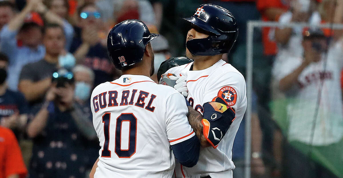 Houston Astros shortstop Carlos Correa (1) celebrates his solo home run with Yuli Gurriel (10) during the second inning of the Astros home opener MLB baseball game at Minute Maid Park, in Houston, Thursday, April 8, 2021.