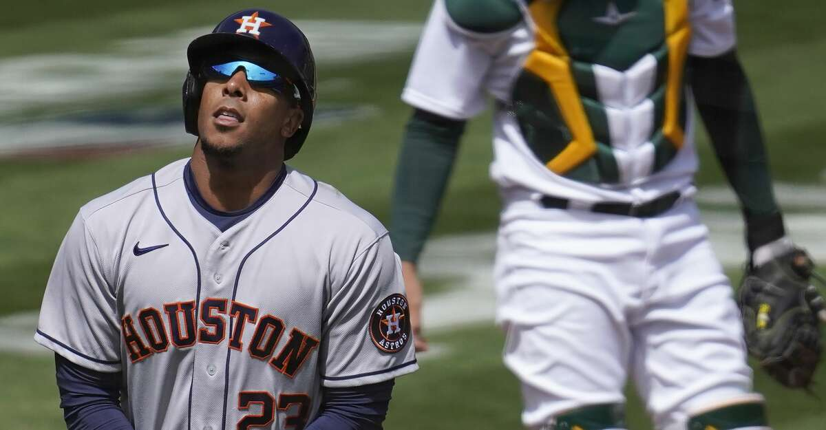 Houston Astros' Michael Brantley, left, reacts after being hit by a pitch in front of Oakland Athletics catcher Aramis Garcia during the first inning of a baseball game in Oakland, Calif., Saturday, April 3, 2021. (AP Photo/Jeff Chiu)