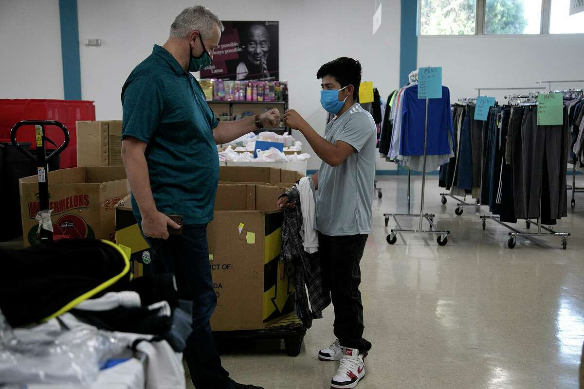 Catholic Charities' J. Antonio Fernández fist-bumps Erick M., 18, recently released from the Freeman Coliseum shelter.