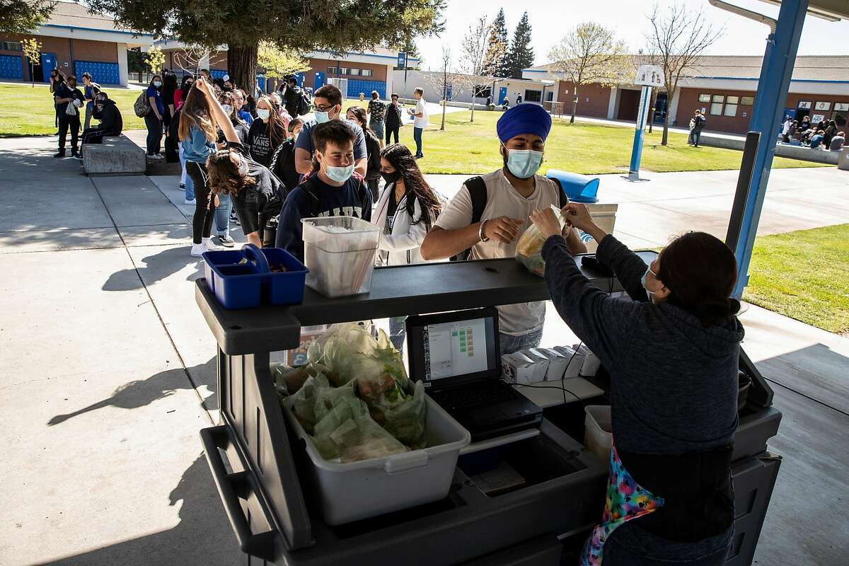Students stand in line to pick up lunch at Sierra High School in Manteca.