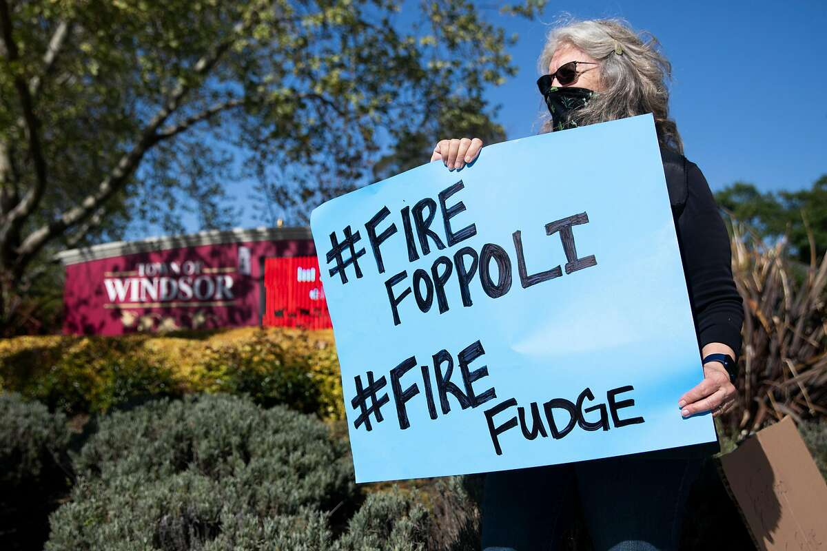 Thirty-year Windsor resident JoAnn Hamilton carries a sign Friday at a rally calling on Windsor Mayor Dominic Foppoli to resign. Some people, including Hamiltion, have also called on Town Councilmember Debora Fudge to resign. The protest came in response to a Chronicle investigation documenting allegations of sexual assault against Foppoli, including a 2017 email describing misconduct that was sent to Fudge. Both denied any wrongdoing.