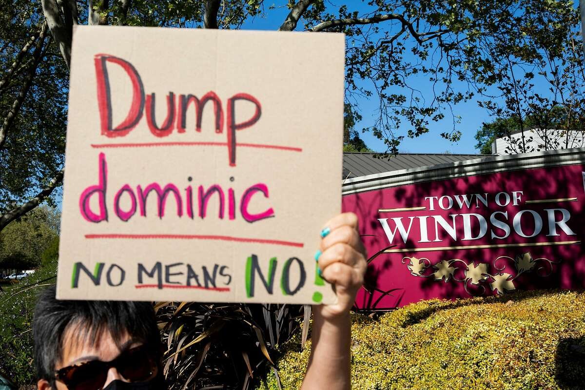 Lillian Fonseca, a 30-year resident of Windsor, carries a sign at an April 9 protest. She said she wants to see Mayor Dominic Foppoli resign over sexual assault allegations, first detailed in a Chronicle investigation.
