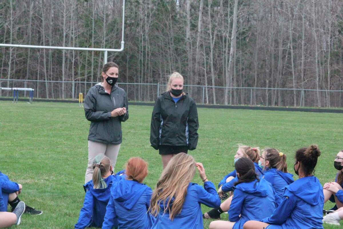 MS girls track coach Ruth Gullekson (back, left) talks to her team after Thursday's meet. (Pioneer photo/John Raffel)