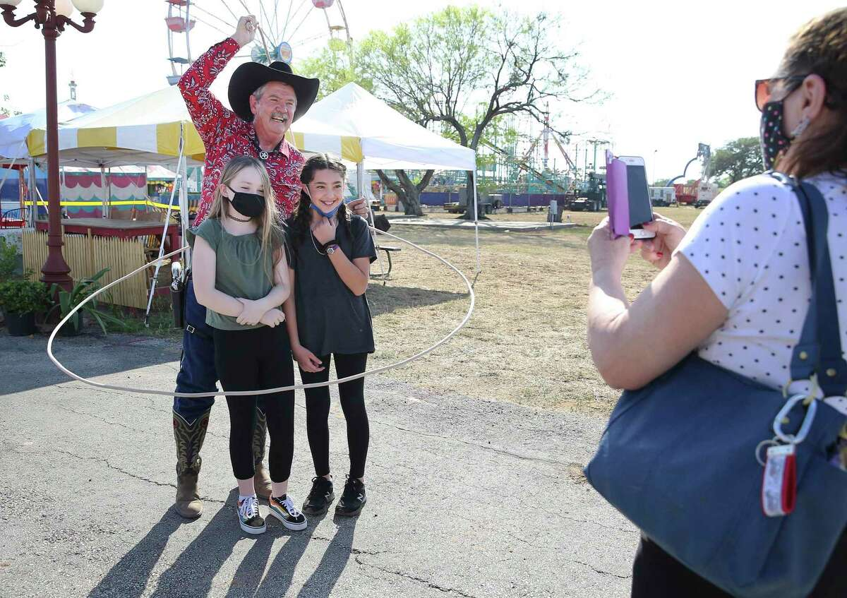 Cowboy Doug Whitaker performs a lasso trick around friends Alyssa Marquez, right, and Allison King as Marquez's mother, Beverly, snaps a picture Friday. The Poteet Strawberry Festival kicked off Thursday evening. It was canceled last year.