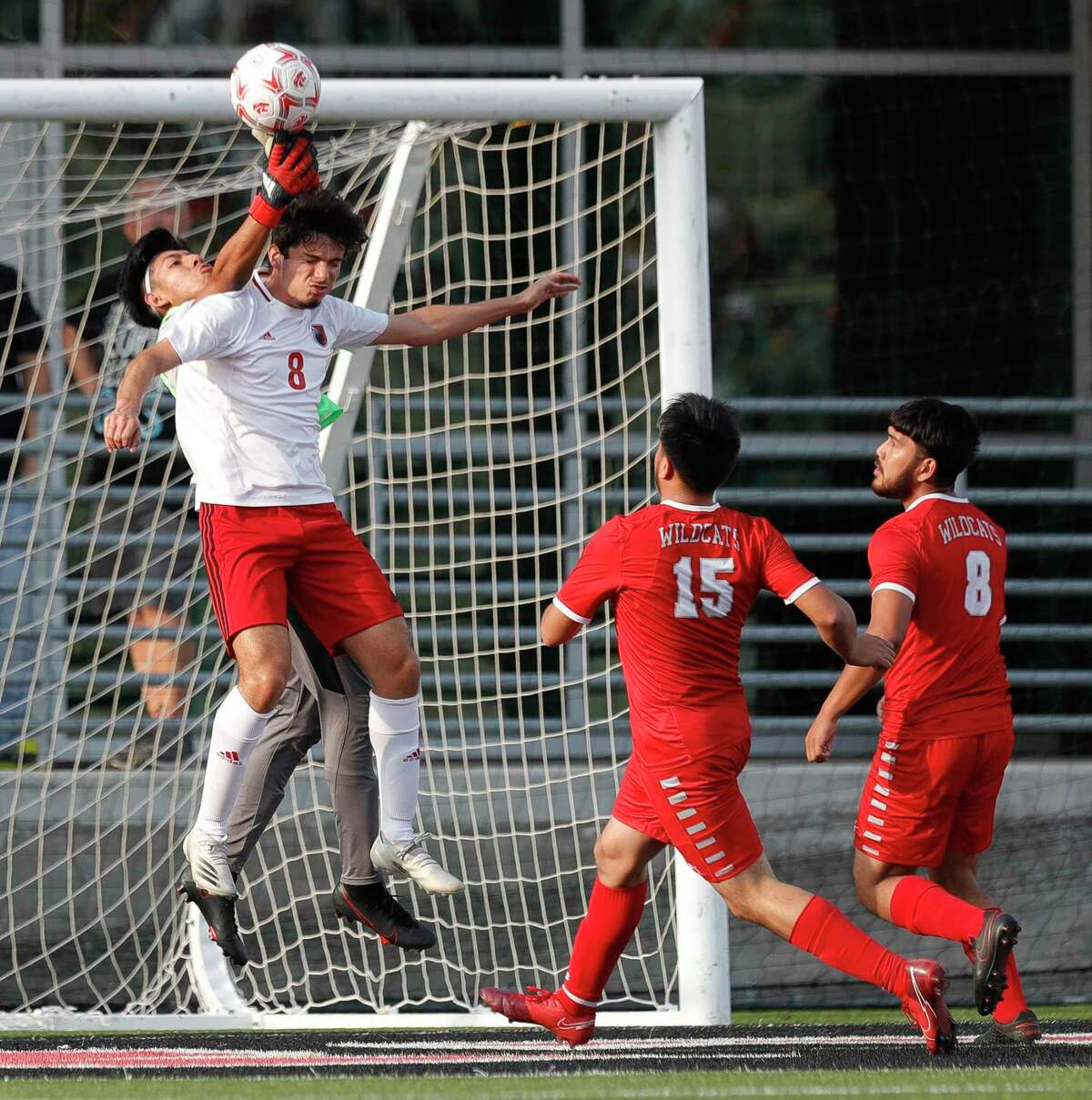 Splendora goalie Ivan Olguin (5) makes a stop as Huffman's Antonio Calzada (8) tried to head in a corner kick during the first period of a Region III-4A championship match at Randall Reed Stadium, Friday, April 9, 2021, in New Caney.