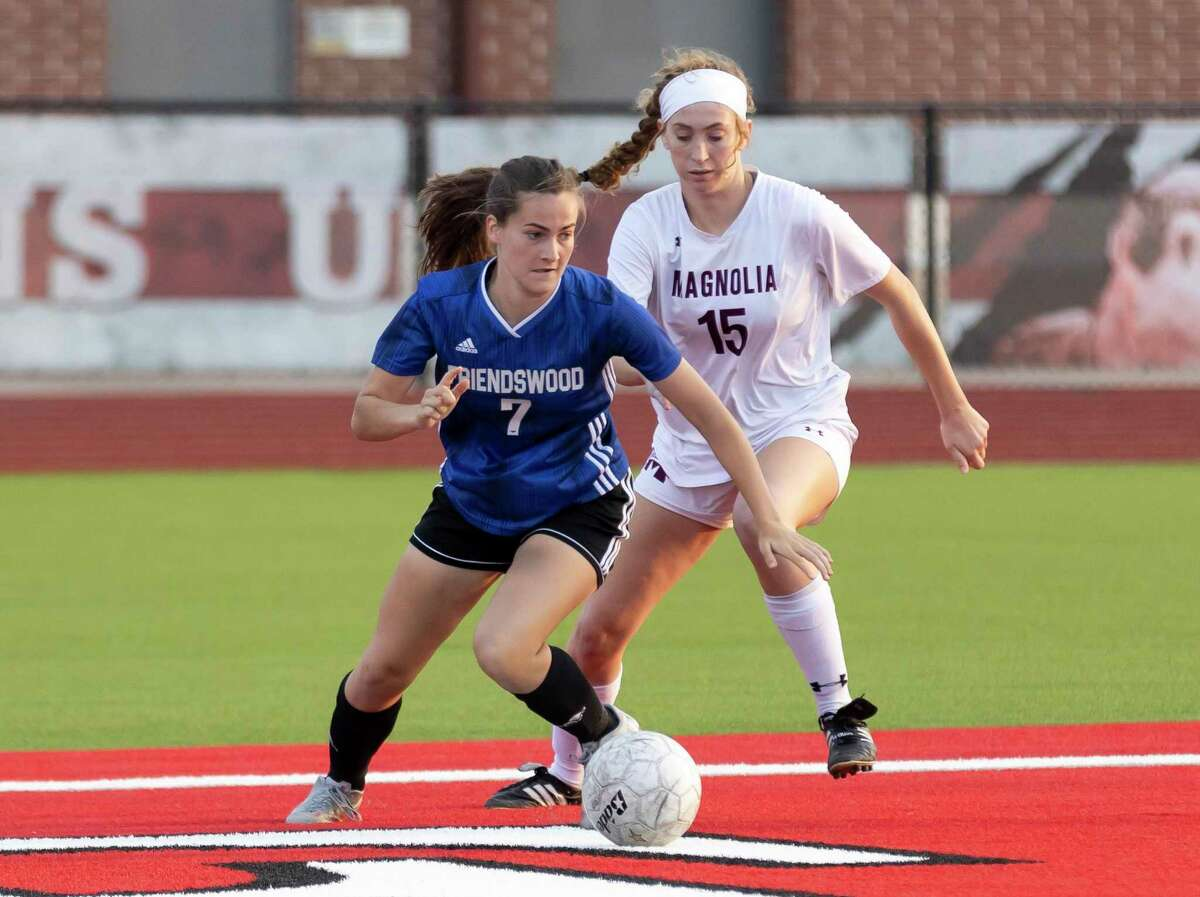 Friendswood Olivia Schmidt (7) drives the ball while under pressure from Magnolia defender Skyler Replogle (15) during the first half of the Region III-5A championship at Falcon Stadium, Friday, April 9, 2021, in Huffman.