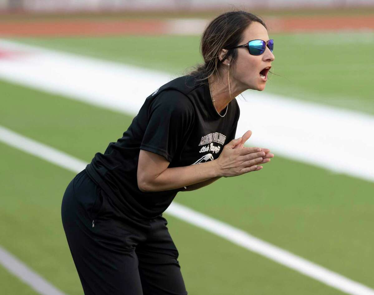 Magnolia head coach April Cleveland calls a play to her team during the first half of the Region III-5A championship against Friendswood at Falcon Stadium, Friday, April 9, 2021, in Huffman.