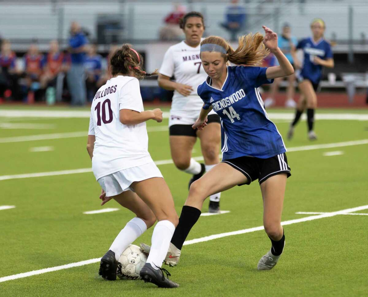Friendswood Brynn Farrar (14) attempts to steal control of the ball from Magnolia midfielder Laney Gonzales (10) during the first half of the Region III-5A championship at Falcon Stadium, Friday, April 9, 2021, in Huffman.