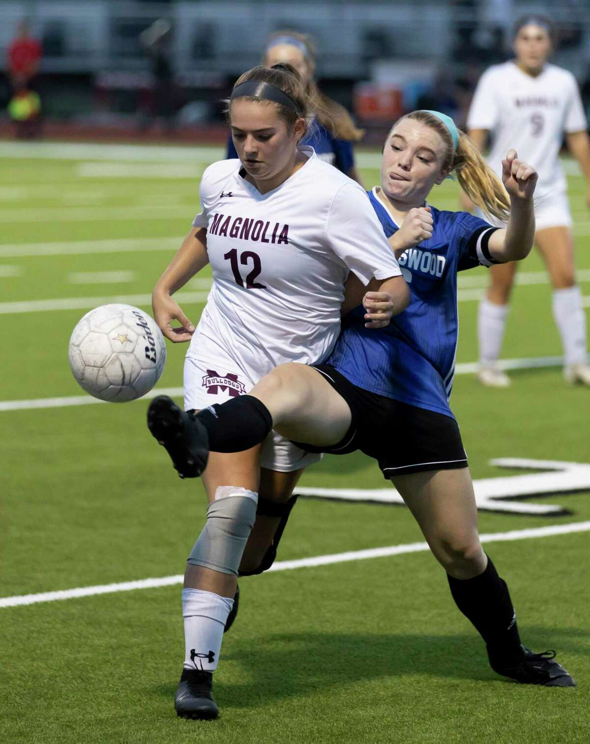 Friendswood Victoria Davis (16) kicks the ball out of control of Magnolia midfielder Elizabeth Ketzner (12) during the first half of the Region III-5A championship at Falcon Stadium, Friday, April 9, 2021, in Huffman.
