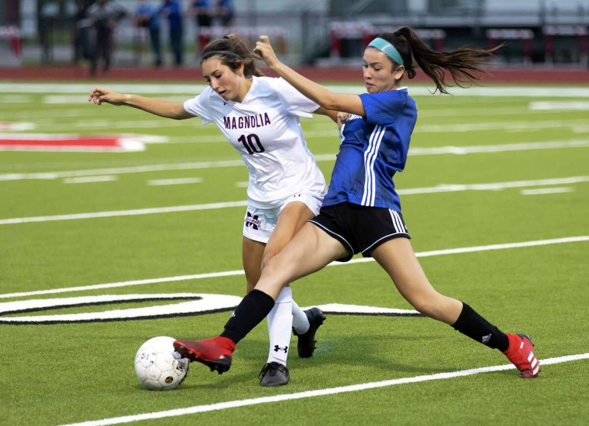 Friendswood Breanna Friberg (10) attempts to kick the ball out of Magnolia defender Danika Etter's (4) control during the first half of the Region III-5A championship at Falcon Stadium, Friday, April 9, 2021, in Huffman.