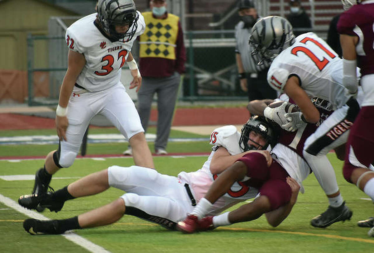Edwardsville's Carson Frosting, bottom, and Chase Parker, right, combine for a tackle in the first quarter on Friday in Belleville.