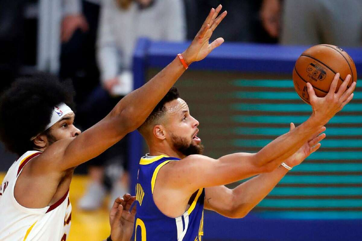 Golden State Warrior Stephen Curry scores past Cleveland Cavalier Jarrett Allen during a game at Chase Center in February.