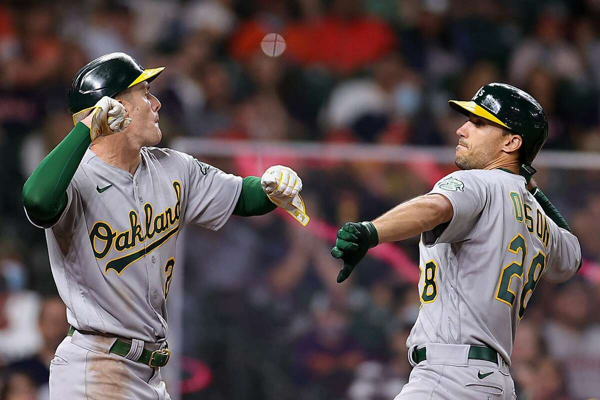 HOUSTON, TEXAS - APRIL 09: Matt Olson #28 and Mark Canha #20 of the Oakland Athletics celebrate during the eighth inning against the Houston Astros at Minute Maid Park on April 09, 2021 in Houston, Texas. (Photo by Carmen Mandato/Getty Images)