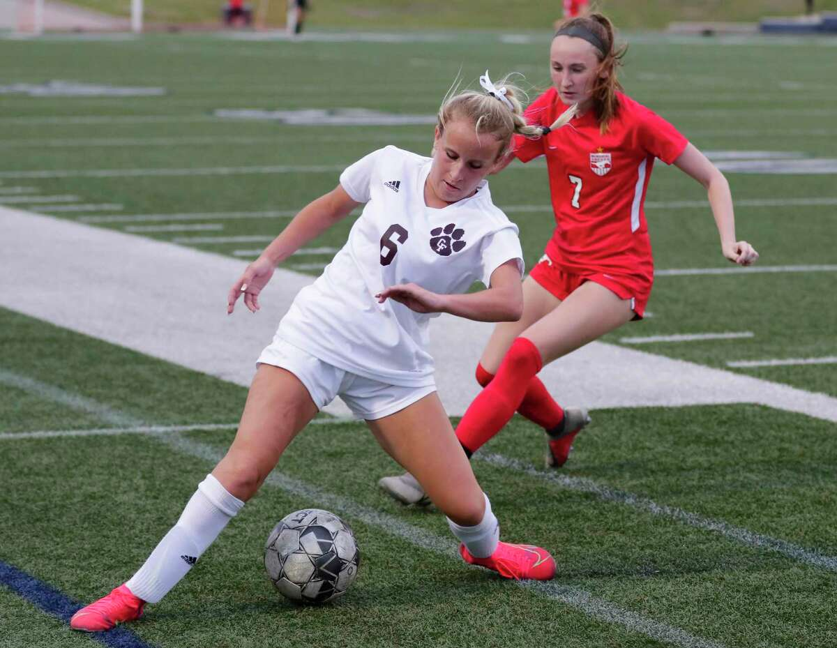 Cy-Fair's Brenley Campbell (6) keeps the ball in bounds in front of Memorial's Ashley Arbour (7) during the second half of their Region 3 championship soccer game Friday, Apr. 9, 2021 at Tully Stadium in Houston, TX.