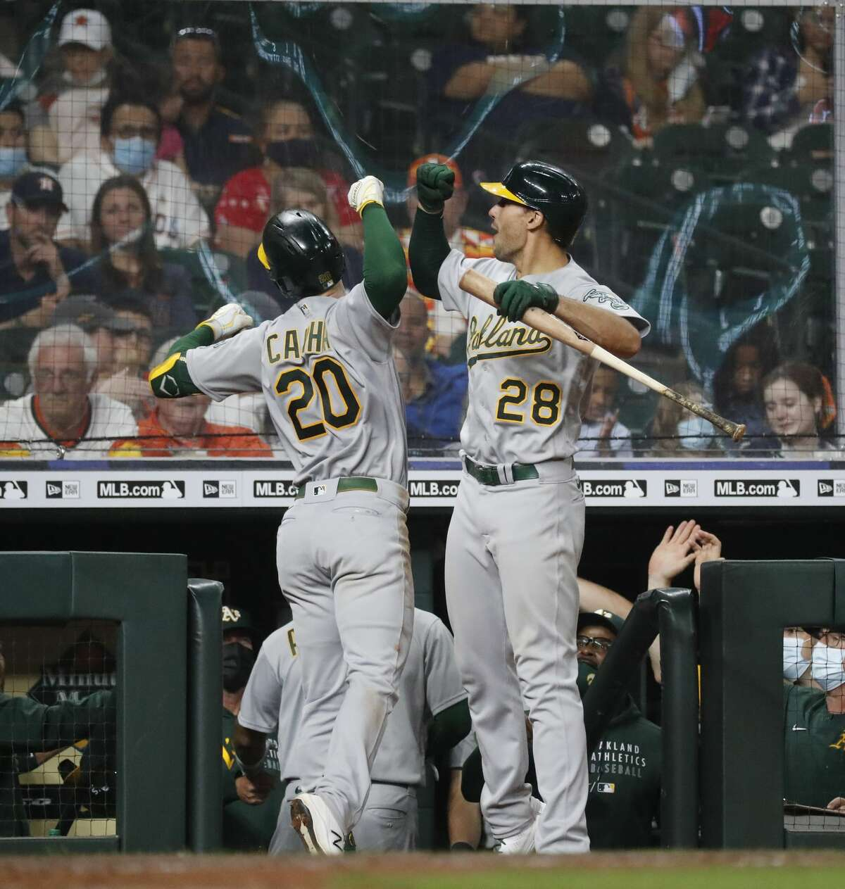 Oakland Athletics Mark Canha (20) celebrates his two-run home run off of Houston Astros relief pitcher Joe Smith with Matt Olson (28) during the ninth inning of an MLB baseball game at Minute Maid Park, in Houston, Friday, April 9, 2021.