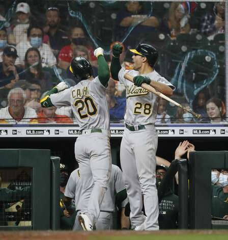 Oakland Athletics Mark Canha (20) celebrates his two-run home run off of Houston Astros relief pitcher Joe Smith with Matt Olson (28) during the ninth inning of an MLB baseball game at Minute Maid Park, in Houston, Friday, April 9, 2021. Photo: Karen Warren/Staff Photographer / @2021 Houston Chronicle