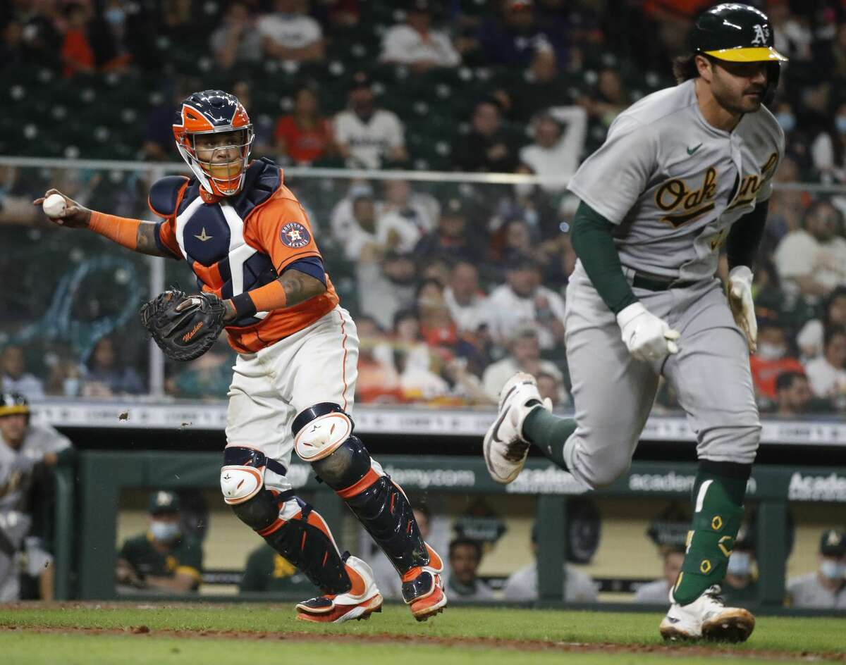 Houston Astros catcher Martin Maldonado (15) makes the throw to first on Oakland Athletics Aramis Garcia's sac bunt during the ninth inning of an MLB baseball game at Minute Maid Park, in Houston, Friday, April 9, 2021.