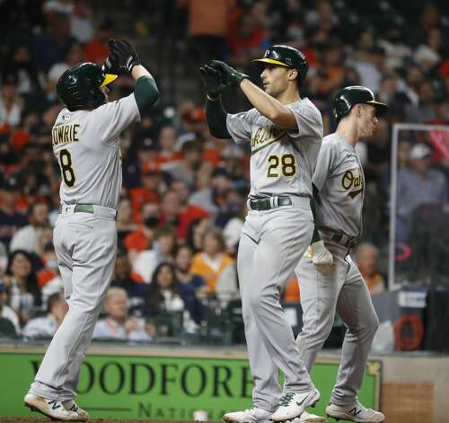 Oakland Athletics Matt Olson (28) celebrates his three-run home with Jed Lowrie (8) during the eighth inning of an MLB baseball game at Minute Maid Park, in Houston, Friday, April 9, 2021. Photo: Karen Warren/Staff Photographer / @2021 Houston Chronicle