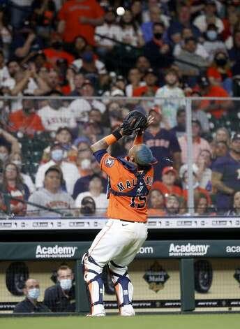 Houston Astros catcher Martin Maldonado (15) catches Oakland Athletics Matt Olson's pop out near the dugout during the sixth inning of an MLB baseball game at Minute Maid Park, in Houston, Friday, April 9, 2021. Photo: Karen Warren/Staff Photographer / @2021 Houston Chronicle