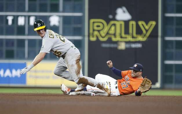 Oakland Athletics third baseman Matt Chapman (26) takes off from second base as Houston Astros second baseman Jose Altuve (27) tried to field a throw from Carlos Correa on Oakland Athletics right fielder Stephen Piscotty's fielders choice during the fourth inning of an MLB baseball game at Minute Maid Park, in Houston, Friday, April 9, 2021. Photo: Karen Warren/Staff Photographer / @2021 Houston Chronicle