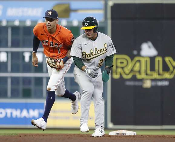 Houston Astros shortstop Carlos Correa (1) catches Oakland Athletics Ramon Laureano (22) stealing second as Jed Lowrie struck out to end the fifth inning of an MLB baseball game at Minute Maid Park, in Houston, Friday, April 9, 2021. Photo: Karen Warren/Staff Photographer / @2021 Houston Chronicle