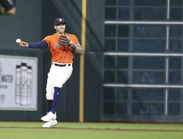 Houston Astros shortstop Carlos Correa (1) makes a throwing error as he tried to field a ball hit by Oakland Athletics Stephen Piscotty (25) during the fourth inning of an MLB baseball game at Minute Maid Park, in Houston, Friday, April 9, 2021. Photo: Karen Warren/Staff Photographer / @2021 Houston Chronicle