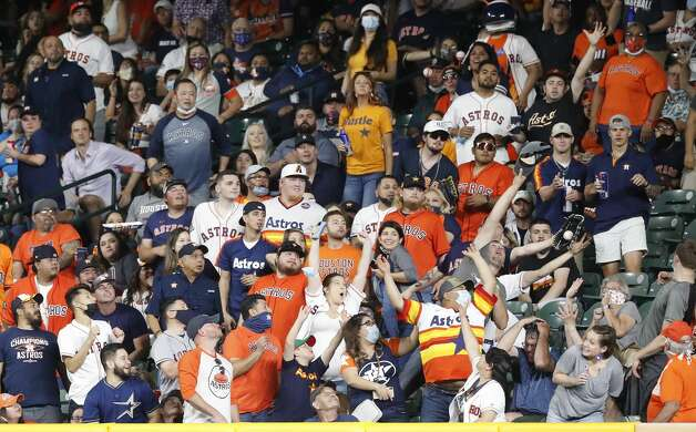 Fans in the right field seats reach for Oakland Athletics Jed Lowrie's home run hit off of Houston Astros starting pitcher Lance McCullers Jr. (43) during the fourth inning of an MLB baseball game at Minute Maid Park, in Houston, Friday, April 9, 2021. Photo: Karen Warren/Staff Photographer / @2021 Houston Chronicle