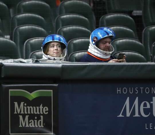A couple with their Astronaut helmets on in the Diamond Club area before the start of the first inning of an MLB baseball game at Minute Maid Park, in Houston, Friday, April 9, 2021. Photo: Karen Warren/Staff Photographer / @2021 Houston Chronicle