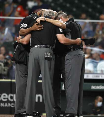 The umpire crew prays before the start of the first inning of an MLB baseball game at Minute Maid Park, in Houston, Friday, April 9, 2021. Photo: Karen Warren/Staff Photographer / @2021 Houston Chronicle