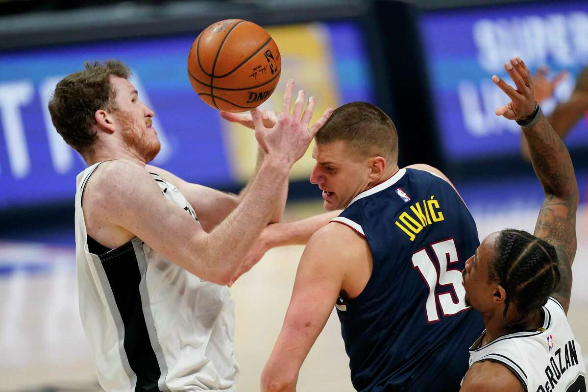 San Antonio Spurs center Jakob Poeltl, left, tries to catch the ball after Spurs forward DeMar DeRozan, right, stripped it from Denver Nuggets center Nikola Jokic, center, in the second half of an NBA basketball game Friday, April 9, 2021, in Denver. (AP Photo/David Zalubowski)