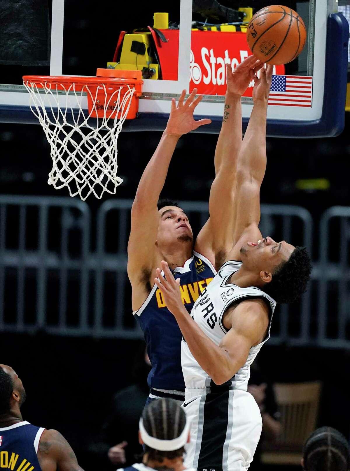 Denver Nuggets forward Michael Porter Jr., left, blocks a last-second shot by San Antonio Spurs forward Keldon Johnson in the second half of an NBA basketball game Friday, April 9, 2021, in Denver. (AP Photo/David Zalubowski)