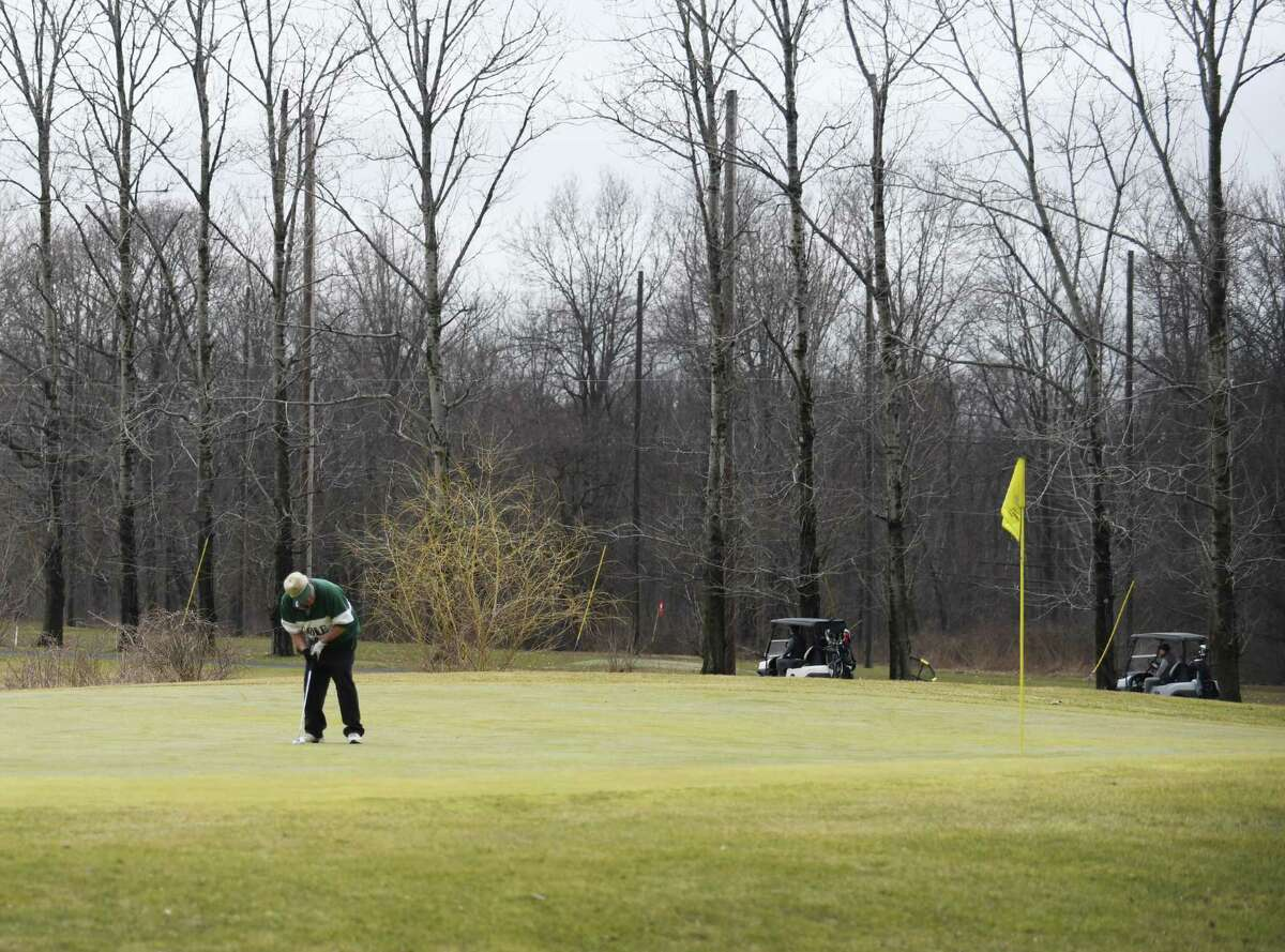 Golfers putt on the green at Griffith E. Harris Golf Course in Greenwich, Conn. Thursday, March 25, 2021.