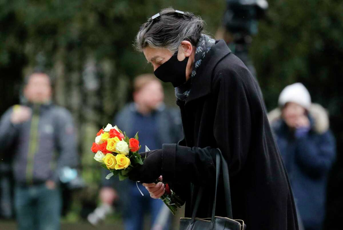 A woman prepares to place flowers outside Windsor Castle, one day after the death of Britain's Prince Philip, in Windsor, England, Saturday, April 10, 2021. Britain's Prince Philip, the irascible and tough-minded husband of Queen Elizabeth II who spent more than seven decades supporting his wife in a role that mostly defined his life, died on Friday.