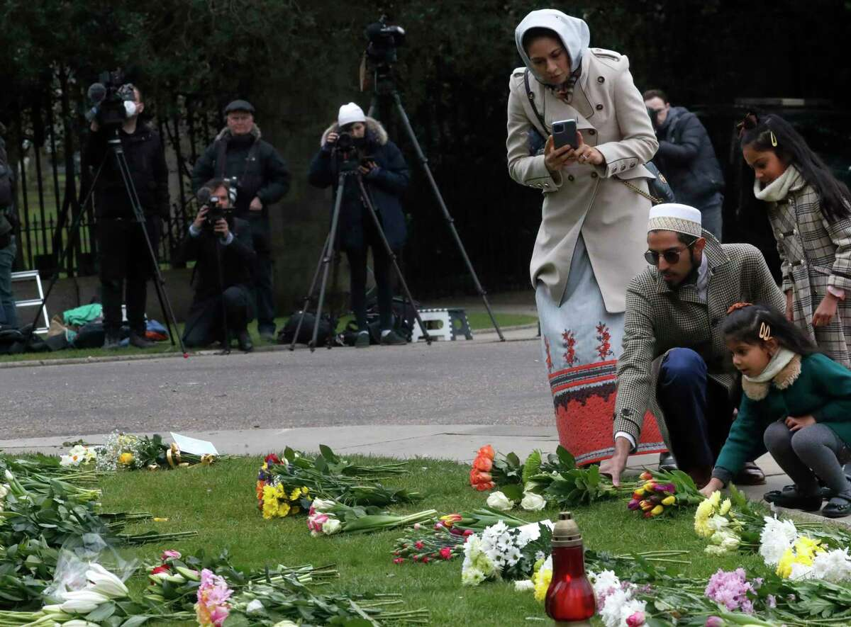 People leave flowers near Windsor Castle, one day after the death of Britain's Prince Philip, in Windsor, England, Saturday, April 10, 2021. Britain's Prince Philip, the irascible and tough-minded husband of Queen Elizabeth II who spent more than seven decades supporting his wife in a role that mostly defined his life, died on Friday.