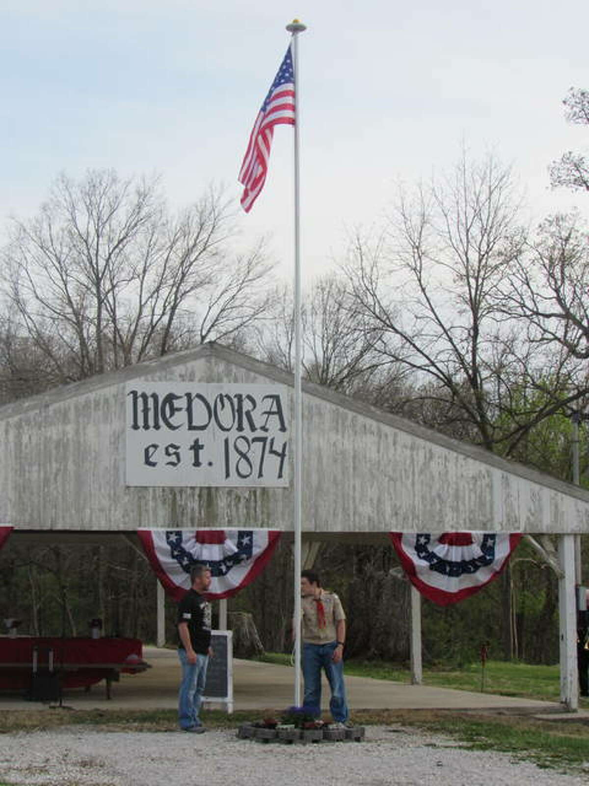 Ken Whitlock, left, with a member of the Medora/Brighton Boy Scouts raise the American flag at Pavilion Park Friday.
