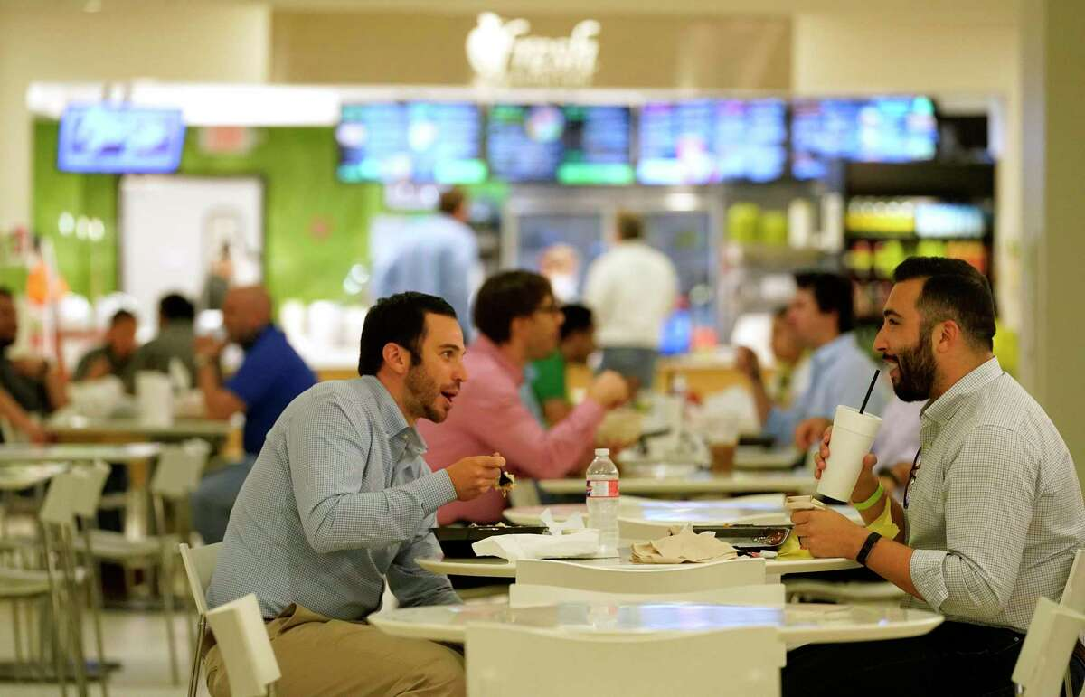 People eat in the food court at One Allen Center, 500 Dallas St., on the tunnel level Thursday, April 8, 2021 in Houston. Business is starting to pick up downtown as offices begin a gradual return to in-person work amid the COVID-19 pandemic.
