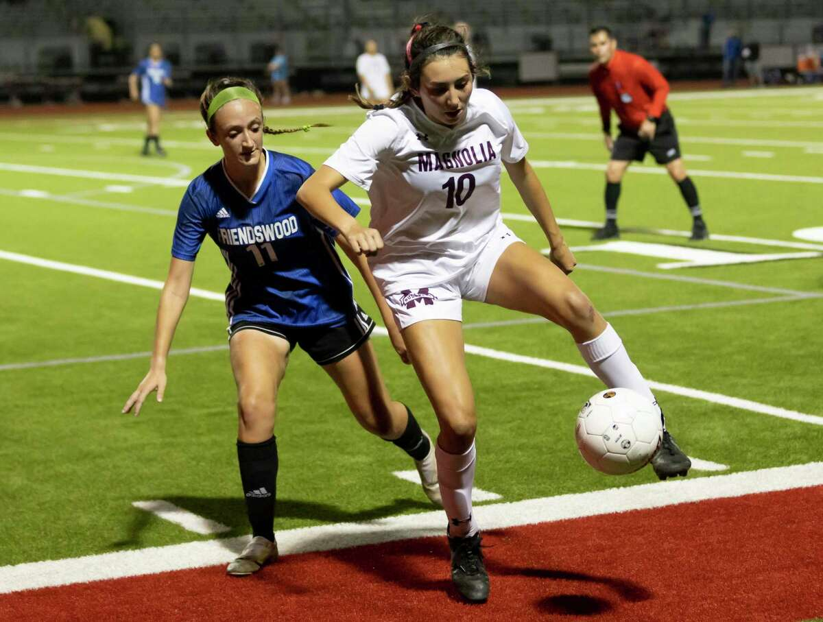 Magnolia midfielder Laney Gonzales (10) takes control of the ball while under pressure from Friendswood Cameryn Peter (11) during the second half of the Region III-5A championship at Falcon Stadium, Friday, April 9, 2021, in Huffman.
